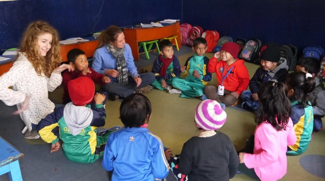 Projects Abroad Childcare volunteers in Nepal sit down with children and play educational games ar a kindergarten.